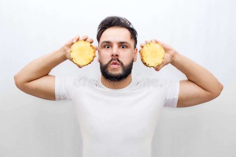 Support et regard vraiment stupéfaits de jeune homme sur la caméra Il oreilles de coveres avec deux halfs d'un ananas Le type est photo libre de droits