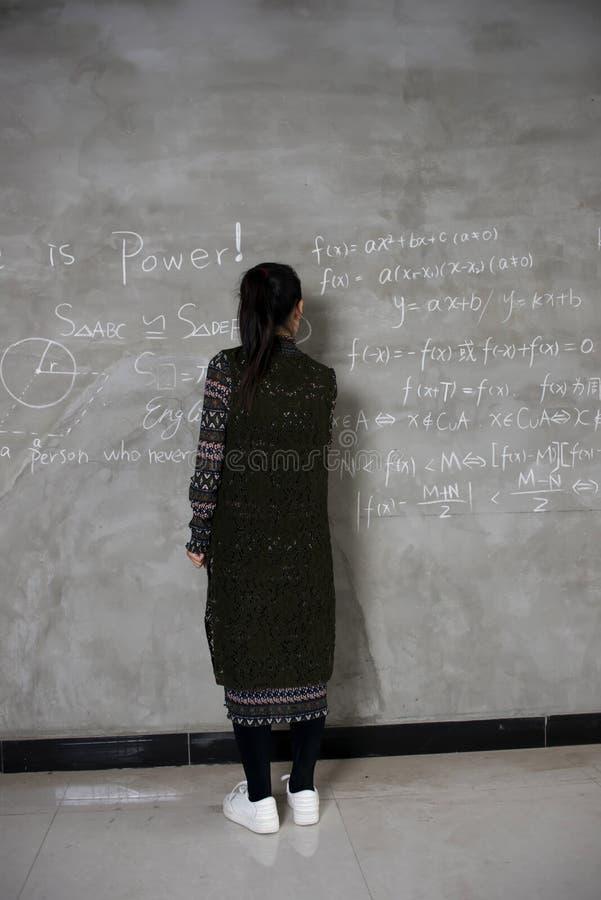 Support femelle d'étudiants universitaires devant l'écriture de tableau noir image libre de droits
