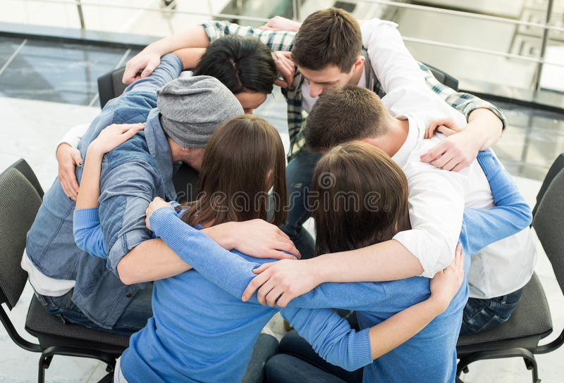 Support Group. Circle of trust. Group of people are sitting embracing in circle and supporting each other stock image