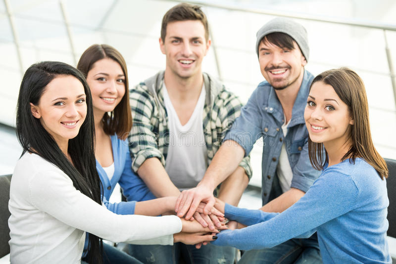 Support Group. Group of young and diverse people are joining hands. Smiling and looking at the camera royalty free stock images