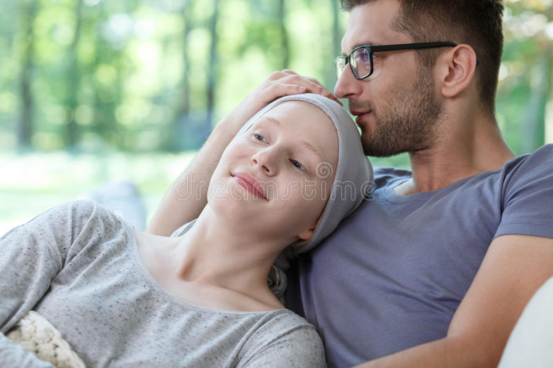 Support in her cancer treatment. Young loving couple supporting each other in her cancer treatment royalty free stock photography