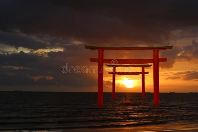 support japonais en bois de pilier de torii de silhouette dessus au-dessus de la mer photo libre de droits