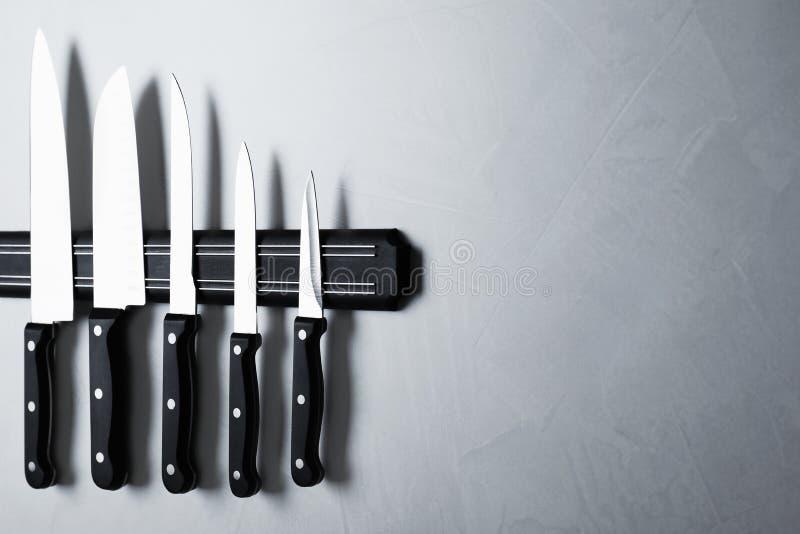 Support magnétique avec l'ensemble de couteaux sur le fond en pierre gris image libre de droits