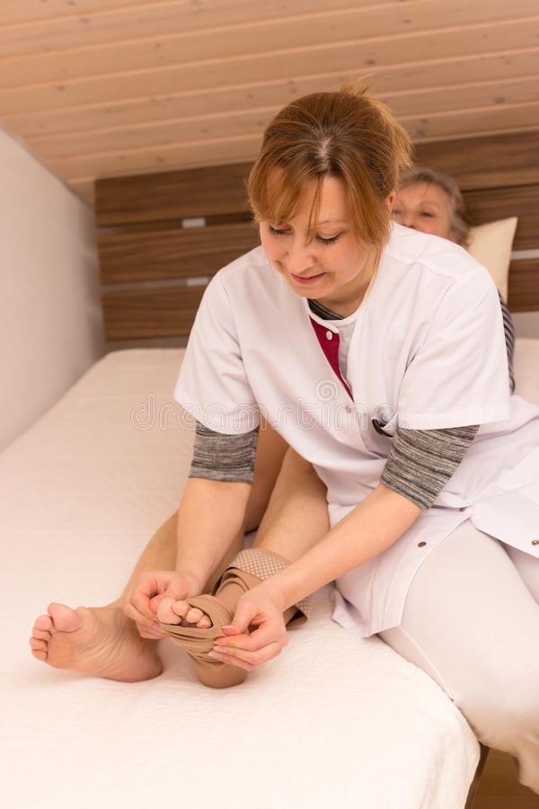 Support in old age. Nurse helps older women in the bed royalty free stock photography