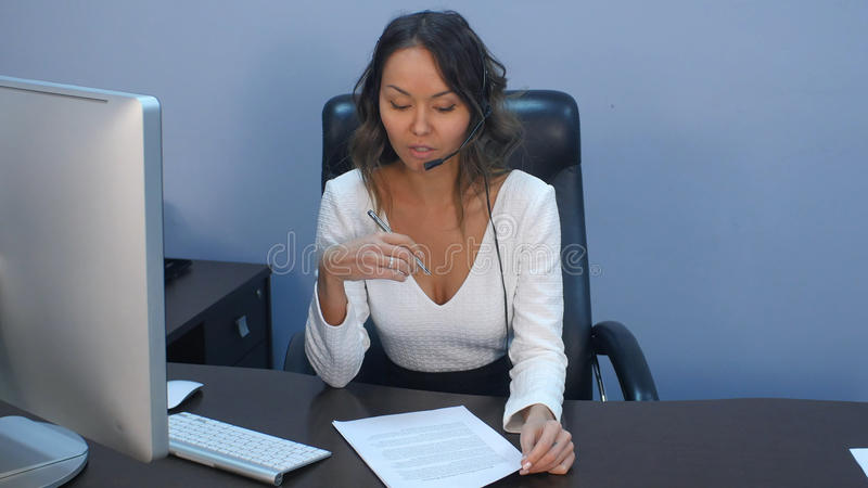Support phone operator in headset working with laptop in office stock photos