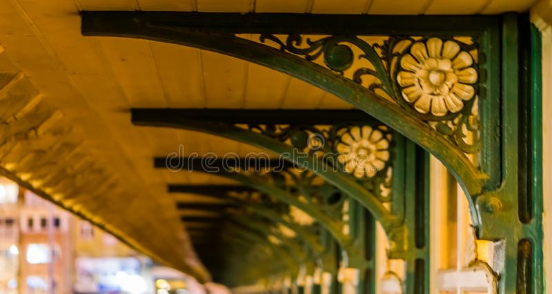 Support pillars of a vintage bus shelter, decorated with white flowers and green plants, classic architecture stock image