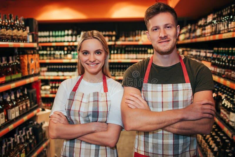 Support professionnel de jeune homme et de femme dans l'épicerie et pose sur la caméra Elle tiennent des mains a croisé et sourir photo stock