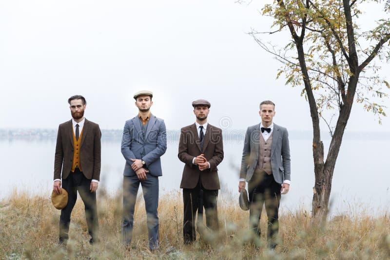 Support sérieux de quatre bandits dans une rangée en automne rétro outdoors photographie stock libre de droits