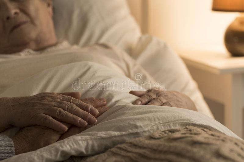 Support during sickness. Close-up of hand of a senior on the hand of dying elderly person as a sign of support during sickness stock photos