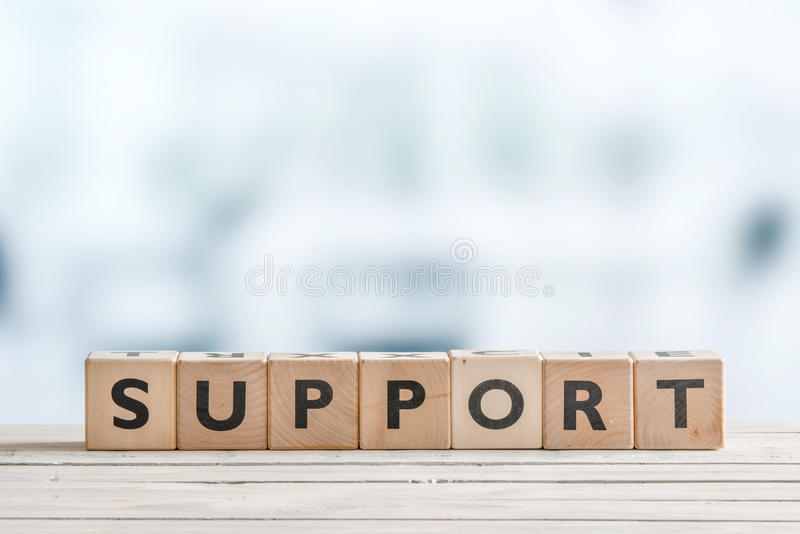 Support sign on a wooden desk stock images
