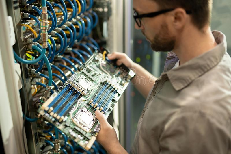 IT support specialist examining motherboard of server royalty free stock image
