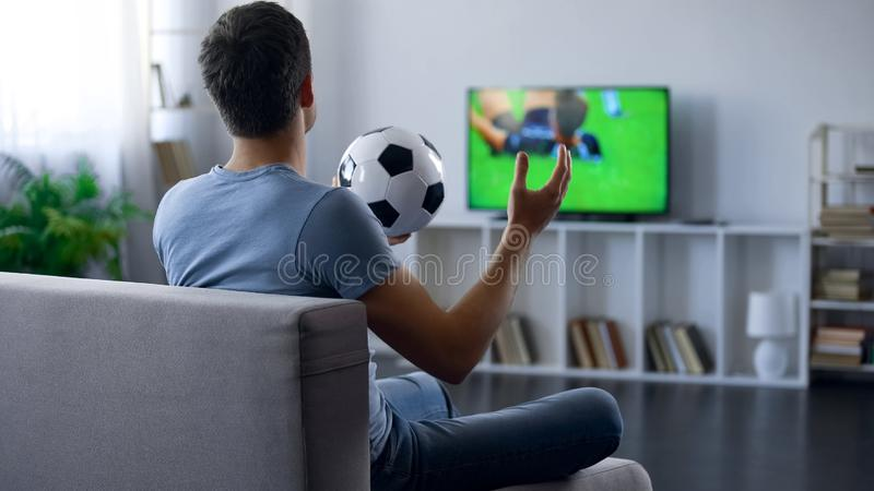 Supporter of soccer team watching game on tv home, unhappy with match result. Stock photo stock photos