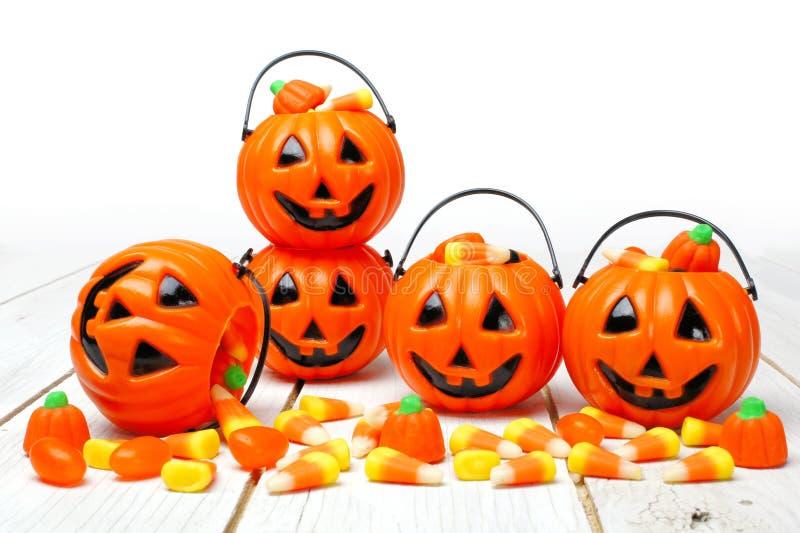 Supporti della caramella della lanterna di Halloween Jack o su legno bianco fotografia stock libera da diritti