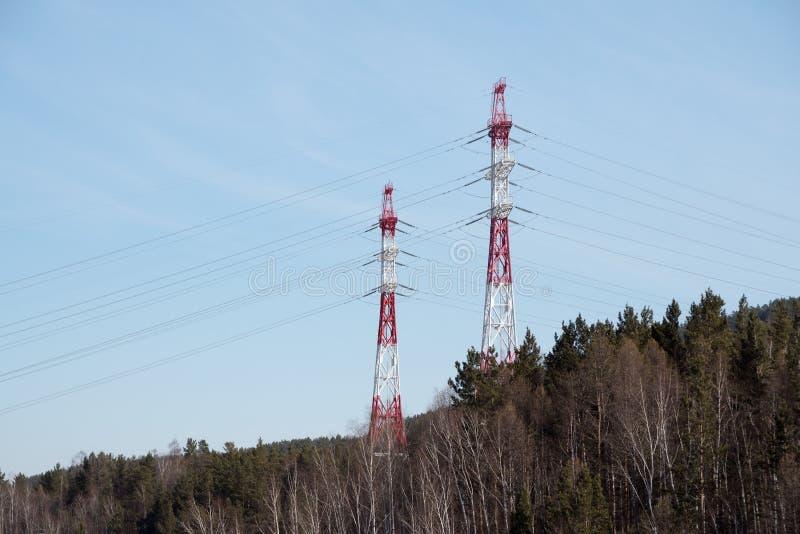 Supporti metallici delle linee elettriche sopraelevate per elettricità, nella collina della foresta, sul cielo blu del fondo fotografia stock