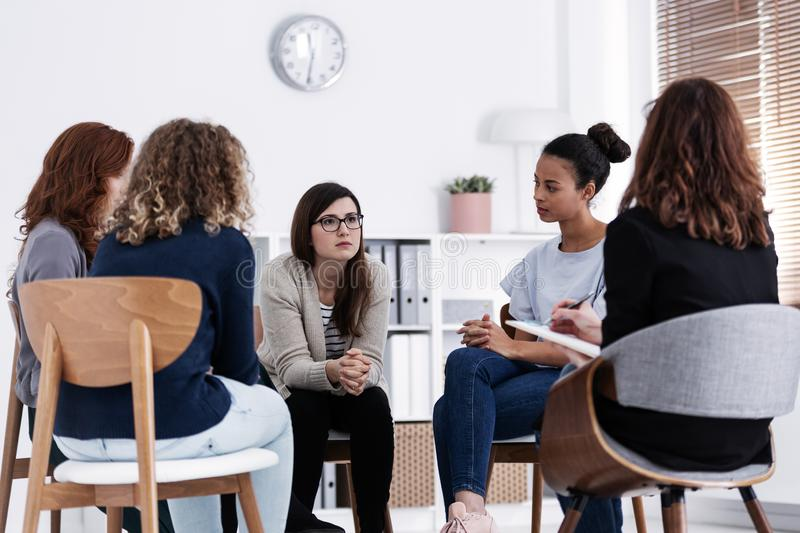 Supporting each other during psychotherapy group meeting. Women supporting each other during psychotherapy group meeting royalty free stock photo