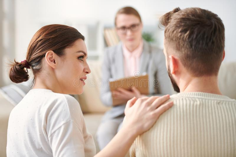 Supporting husband. Young supportive wife looking at her husband while keeping hand on his shoulder during their visit to counselor office royalty free stock images