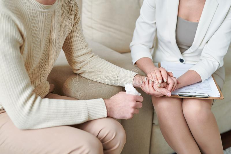 Supporting patient. Supportive counselor holding hand of miserable patient with handkerchief while comforting him at session royalty free stock image