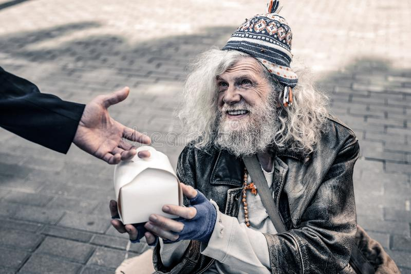 Dirty grey-haired senior homeless wearing ragged clothes and receiving food stock images