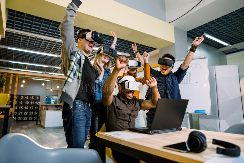 Supportive group of young diverse multiracial business people wearing vr goggles celebrating their victory in creative royalty free stock image
