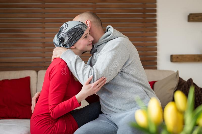 Supportive husband kissing his wife, cancer patient, after treatment in hospital. Cancer and family support. royalty free stock images