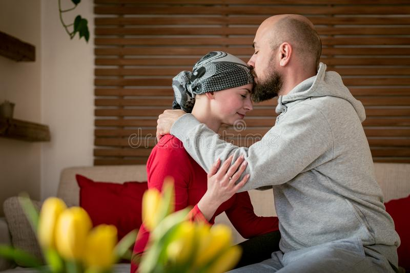 Supportive husband kissing his wife, cancer patient, after treatment in hospital. Cancer and family support. Supportive husband kissing his wife, cancer patient royalty free stock images