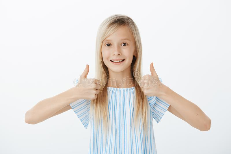 Supportive little friend wants to cheer mates. Happy positive cute girl with blond hair, raising thumbs up and giving stock photo