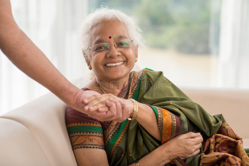 Supportive spouse. Portrait of happy senior woman holding hand of her spouse royalty free stock photos