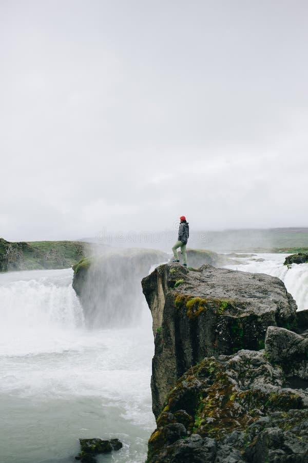 Supporto avventuroso dell'uomo sul bordo della cascata della scogliera fotografia stock libera da diritti