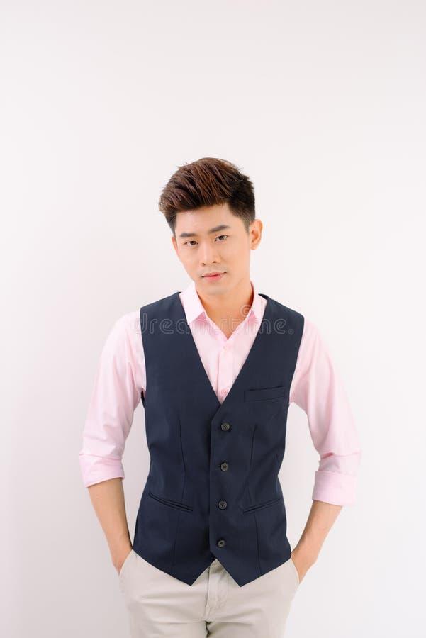 Supporto bello e sorriso asiatici dell'uomo che posano sul fondo grigio fotografie stock libere da diritti