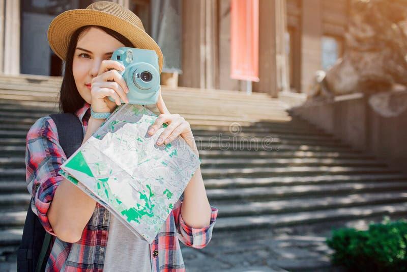 Supporto castana piacevole ed adorabile fuori Il viaggiatore tiene la macchina fotografica blu e le pose Inoltre ha mappa in mani immagine stock libera da diritti