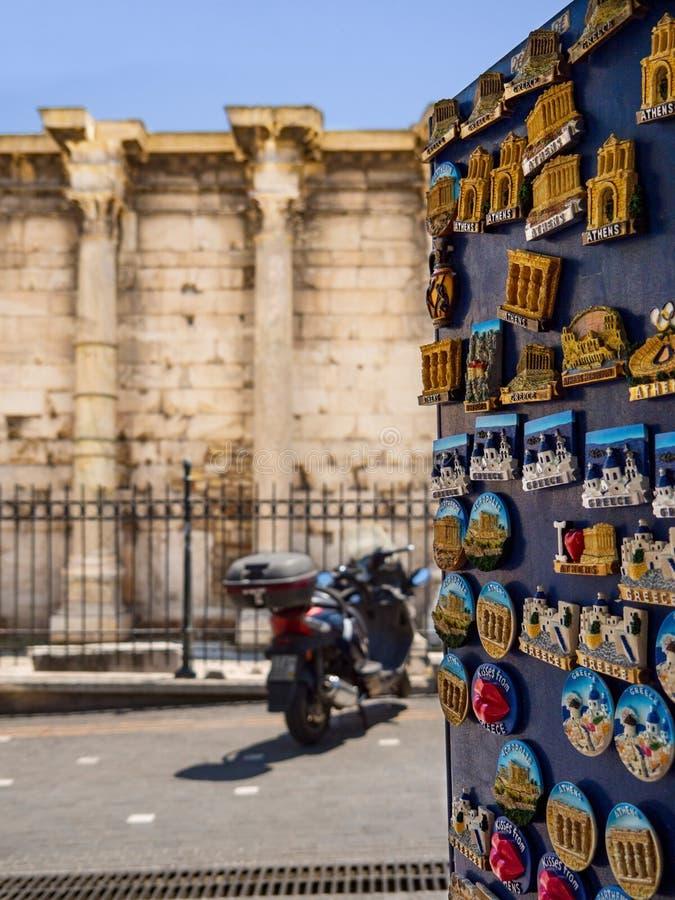 Supporto con i magneti turistici di fronte alla biblioteca di Hadrian nella zona turistica di Monastiraki fotografia stock libera da diritti