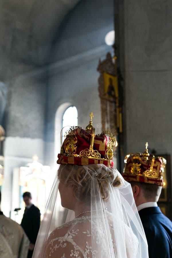 Supporto coronato dello sposo e della sposa nella chiesa fotografie stock