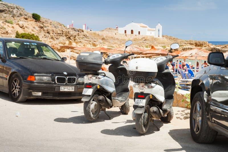 Supporto dei motorini parcheggiato fra le automobili immagine stock libera da diritti