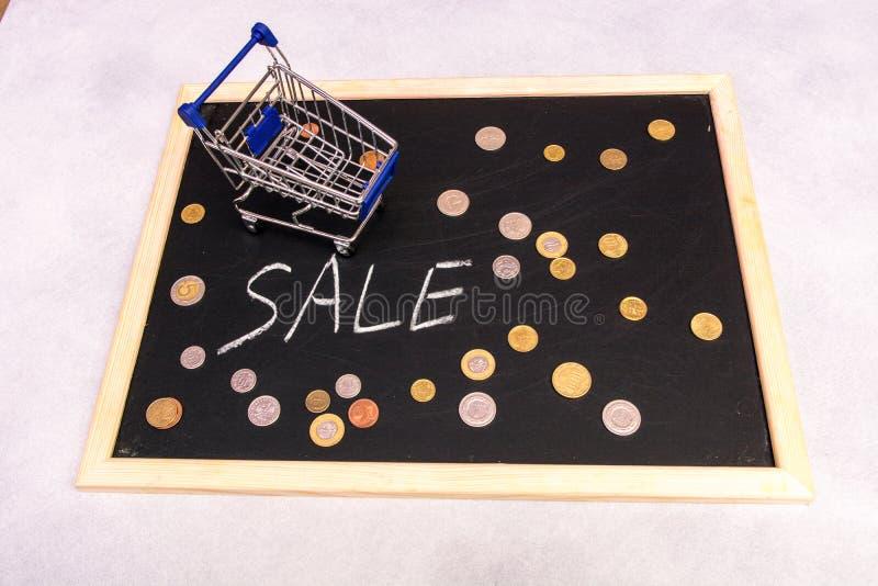 Supporto del carrello di acquisto sulla lavagna con le monete e il ` di vendita del ` del testo fotografia stock libera da diritti