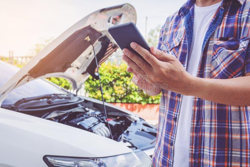 Supporto dell'uomo dell'Asia anteriore un'automobile rotta che chiama per assistenza fotografia stock libera da diritti