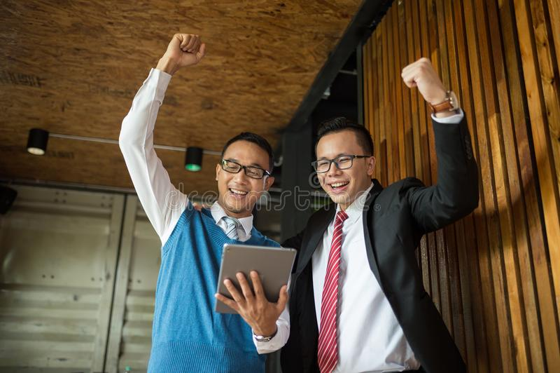Supporto dell'uomo d'affari di due asiatici ed esaminare compressa, essi allegri e celebrati il suo riuscito nella missione fotografie stock libere da diritti