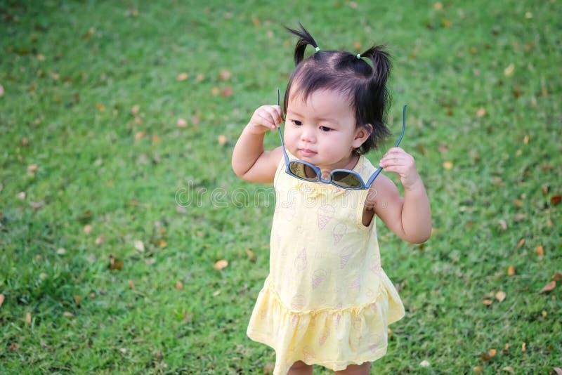 Supporto della bambina del primo piano con gli occhiali da sole sul pavimento dell'erba nei precedenti del parco con lo spazio de immagini stock libere da diritti