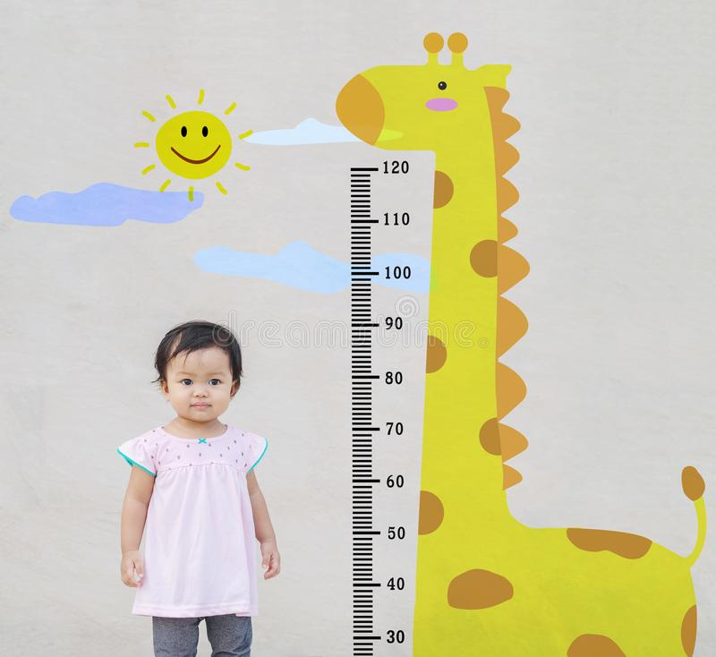 Supporto della bambina del primo piano per altezza di misura con il fumetto sveglio della giraffa ai precedenti strutturati di ma fotografia stock libera da diritti