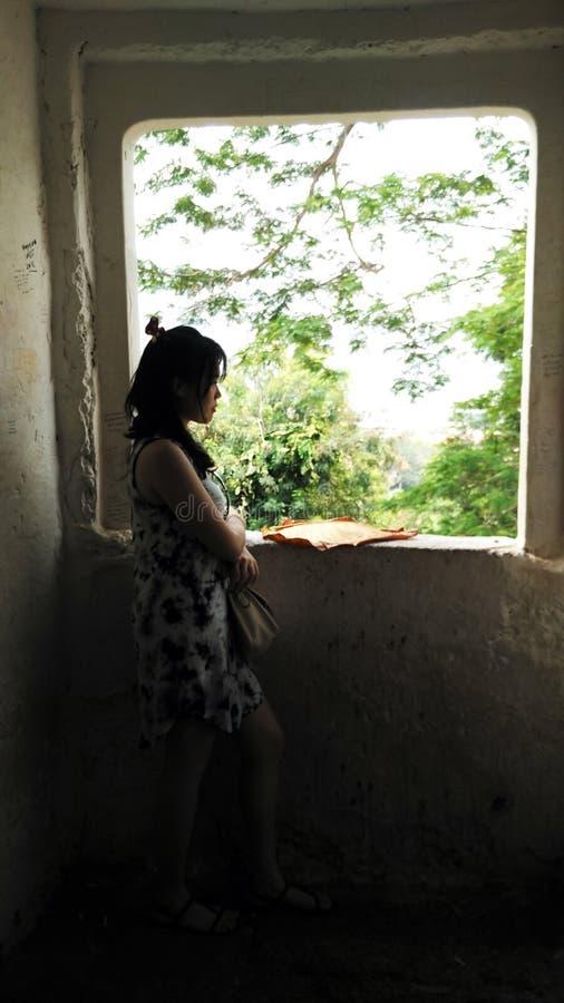 Supporto della giovane donna alla finestra scura fotografia stock