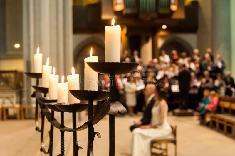 Supporto di candela con le candele e gente vaga in chiesa immagine stock