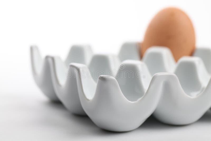 Supporto di ceramica dell'uovo con l'uovo marrone del pollo fotografia stock libera da diritti