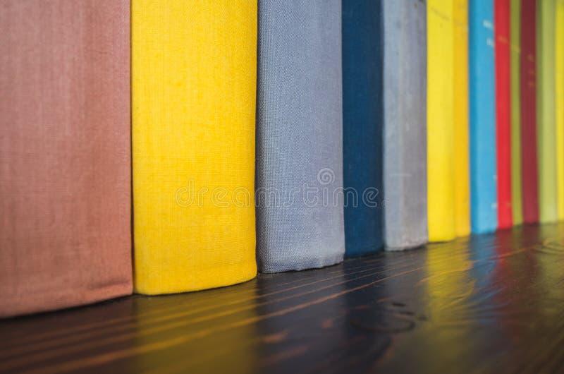 Supporto di libri variopinto in una fila su uno scaffale fotografia stock libera da diritti