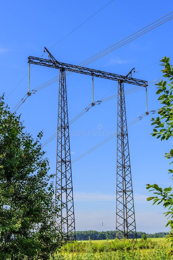 Supporto e cavi di una linea di trasmissione ad alta tensione sopra un campo verde nella mattina di inizio dell'estate fotografia stock libera da diritti