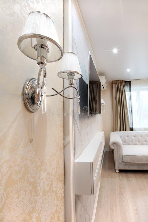 Supporto a mensola sulla parete con la TV nel salone - interno luminoso fotografia stock libera da diritti