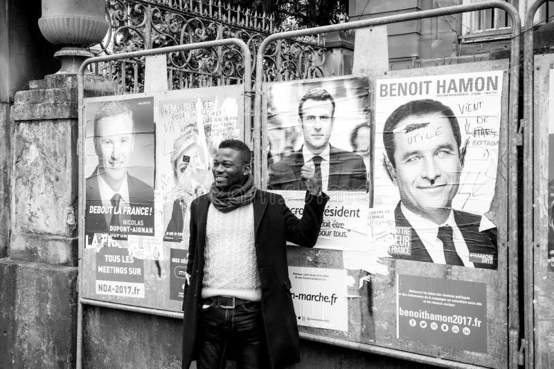 Supporto nero di rappresentazione dell'uomo di etnia ad Emmanuel Macron immagini stock