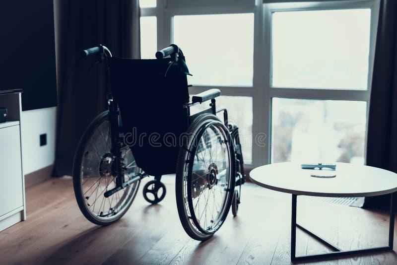 Supporto vuoto moderno della sedia a rotelle vicino alla finestra nella sala immagine stock libera da diritti