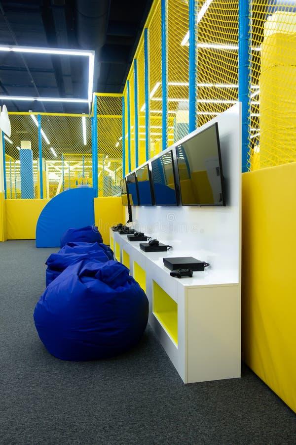 Supports avec les consoles du jeu des enfants et les TV au centre de divertissement des enfants Chaises frameless molles image stock