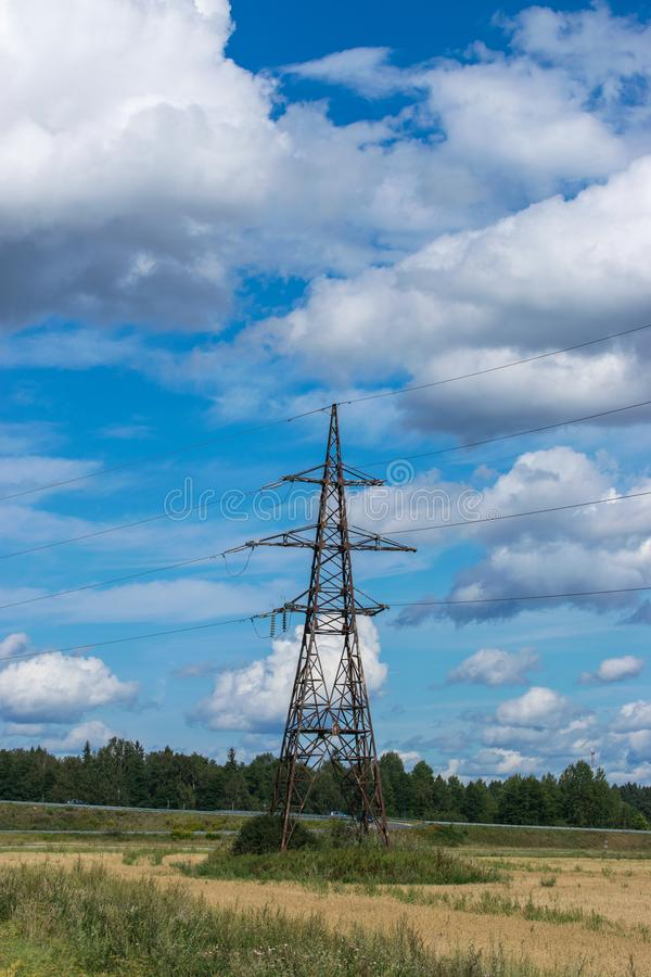 Supports high-voltage power lines against the blue sky with clouds. Electrical industry stock image