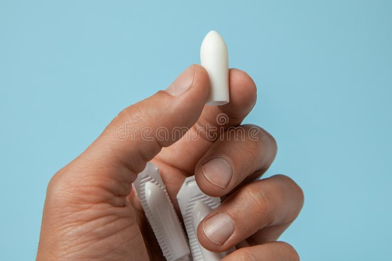 Suppository for anal or vaginal use in the hands of a man. Candles for treatment of hemorrhoids, temperature, thrush. Inflammation royalty free stock image