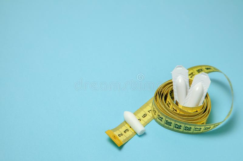 Suppository for anal or vaginal use and yellow measuring tape. Candles for the treatment of obesity, extra weight, for weight loss. Copy space for text royalty free stock photography